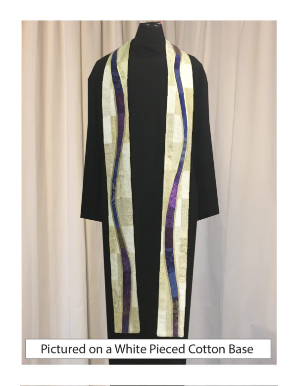 """Pieced cotton base embellished with gently meandering """"rivers"""" of a selection of cottons in a range of prints, solids, and batiks in blue and purple tones outlined with solid bias trim to resemble bread and wine."""